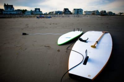 Two hard paddle boards lay face down in the sand at the beach