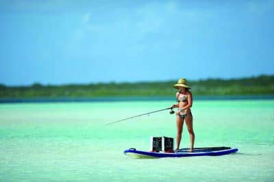 Young woman in a bikini and a straw hat fishes off of an SUP in shallow, tropical green waters