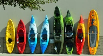 An assortment of short and tall kayaks standing on end against a wall