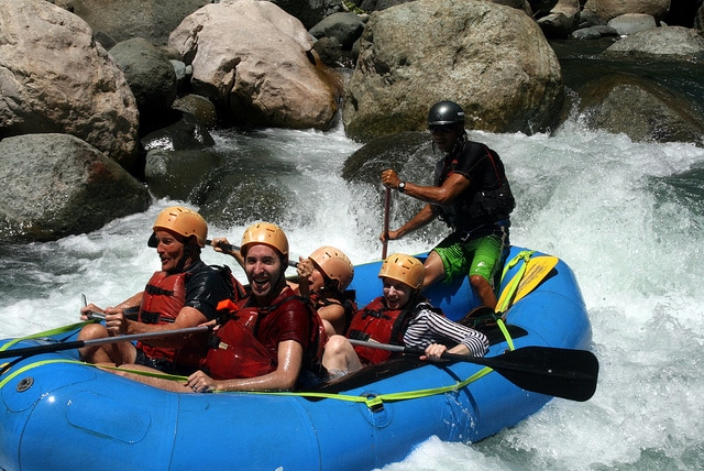 A sturdy whitewater raft navigates rocky rapids. Inflatable kayaks are often made of the same durable materials as these rafts.