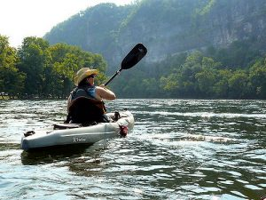 Tall woman in a cowboy hat paddles a big kayak in a lake near the mountains