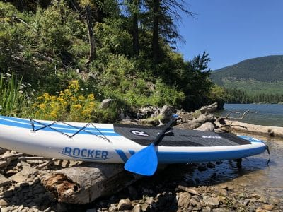 Picturesque side photo of the iRocker paddle board as it lays upon a log on a rocky shore