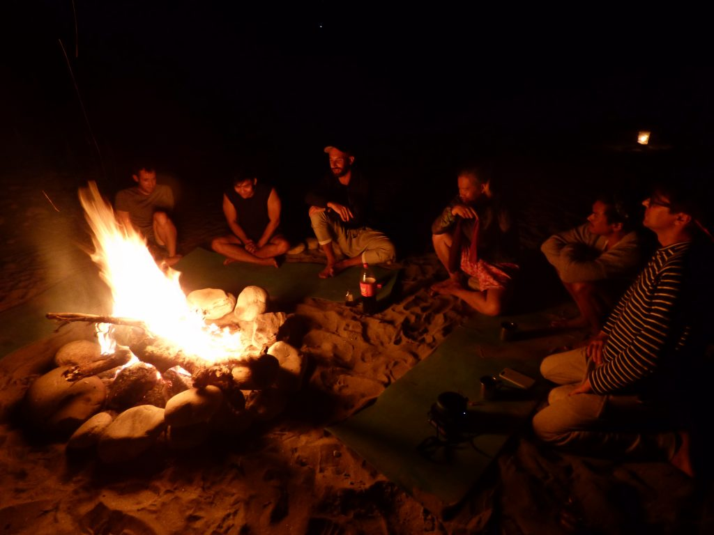 Post-rafting relaxation around a campfire after a guided day excursion with River and Soul Adventures in Nepal
