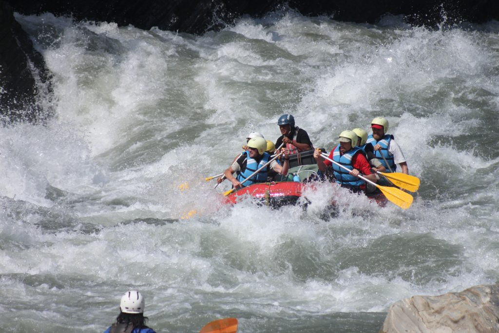 A group of rafters goes through some wild rapids in the foothills of the Himalayas