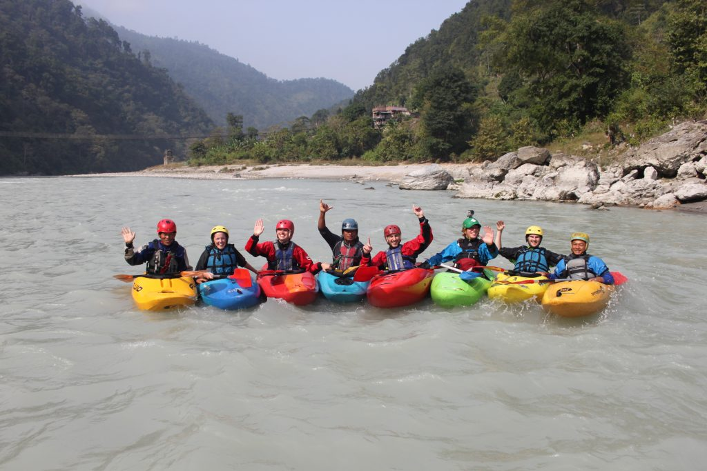 Group photo of all the river guides on their whitewater kayaks after another epic excursion in Nepal