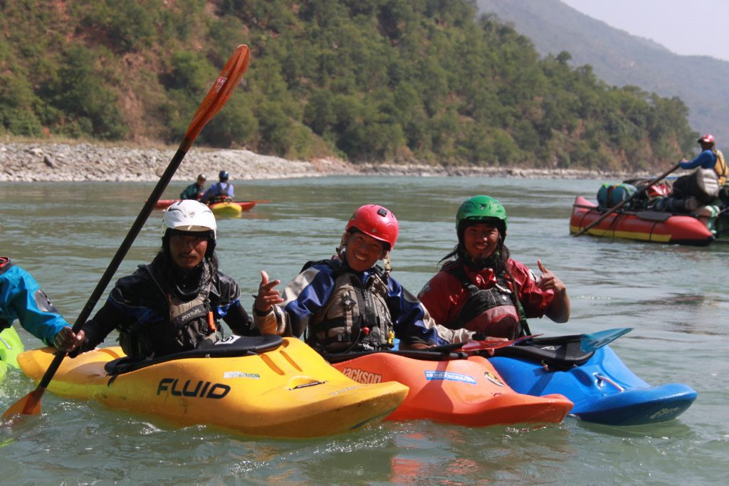 3 Nepali river guides smile and pose in their small whitewater kayaks