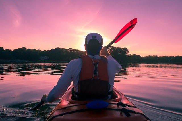 Backseat photo of man in the bow of a tandem kayak paddling into the sunset