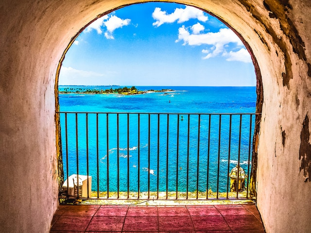 Scenic view of tropical blue waters taken from inside a tunnel built into the wall of an old fortress