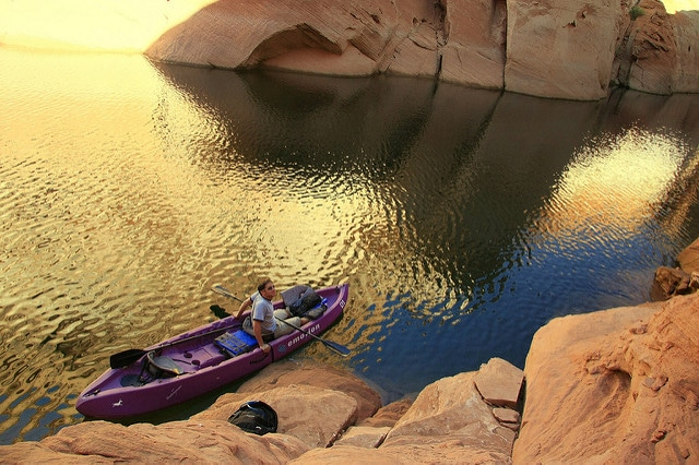 Man in a large double kayak waits beside a steep, rocky cliff in Arizona
