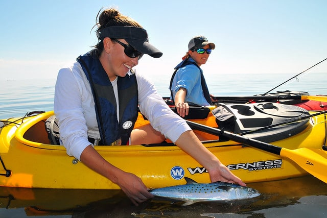 Two women sit in their sit inside kayaks. The woman the foreground shows off the fish she just caught.