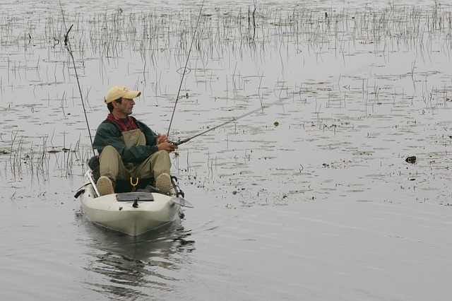 Man sits on his sit on top kayak fishing in a grassy marsh