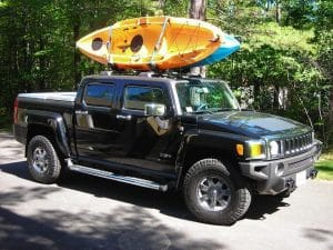 A sport utility vehicle is parked with a roof rack on top of the vehicle holding two kayaks