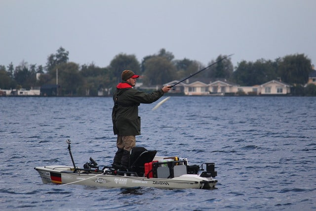 Man stands on a hybrid kayak in cold weather gear casting a fishing line