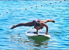 Woman does an arm balance yoga pose on her paddle board