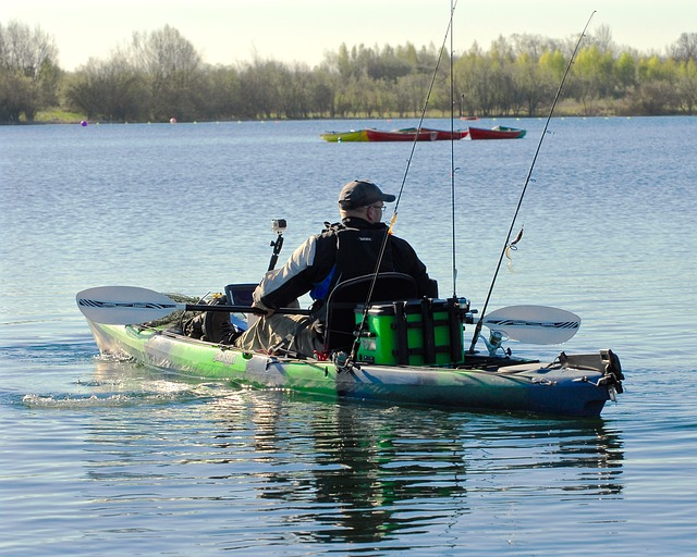 Man paddles a kayak decked out in fishing gear -- cooler, rods, Go Pro mount, fish finder and more
