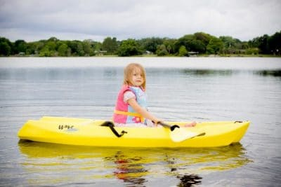 Little girl paddles a small, kid-sized kayak on a calm lake
