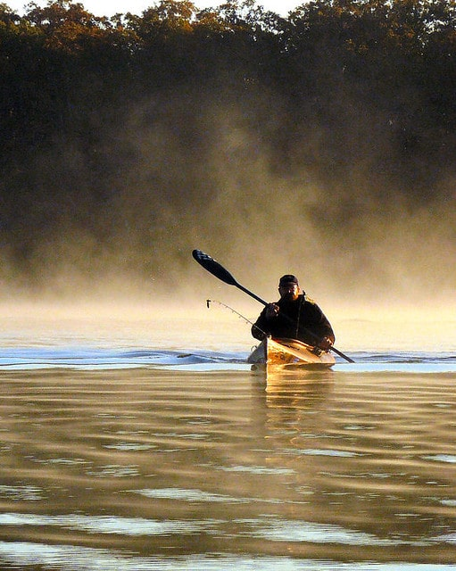 Kayak angler paddles to his spot first thing in the morning as the fog rises off the water