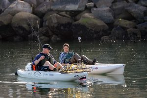 Two kayak anglers paddle to their fishing spot