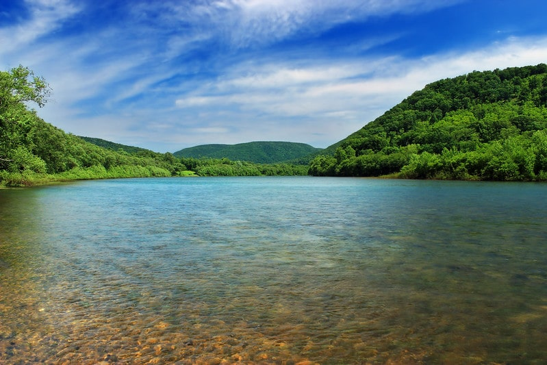 Lush green trees on hilly landscapes line the shallow, rocky bottom shores of the Susquehanna River.