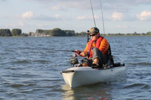 Man in a decked out angling kayak uses a fish finder to locate fish while he fishes offshore in the ocean