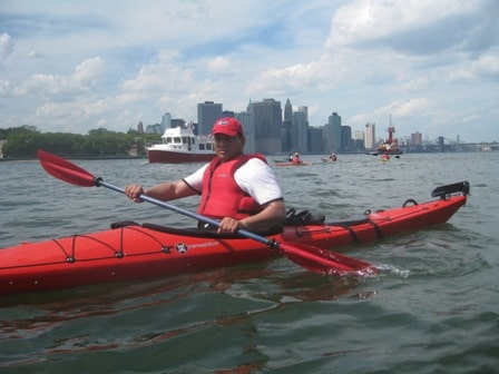 Man in a red hat, red vest, and red kayak paddles the busy waters near NYC