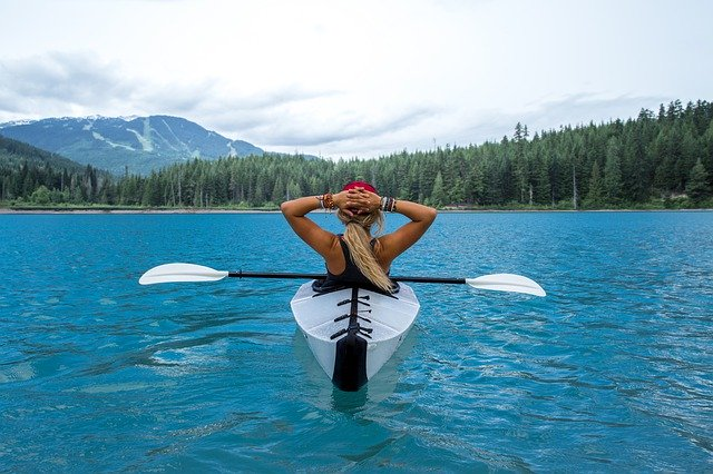 Young woman takes in the mountain scenery while she takes a break from paddling her foldable kayak