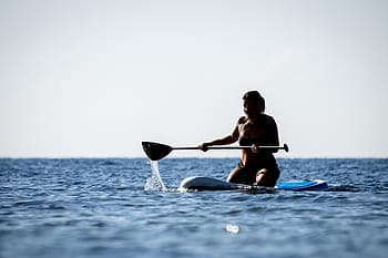 Woman in a bikini kneels while paddling an SUP in the ocean