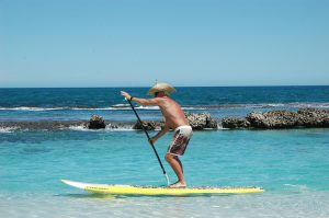 Shirtless man in a straw hat does a powerful forward stroke on an SUP in shallow waters near a rock wall in the ocean
