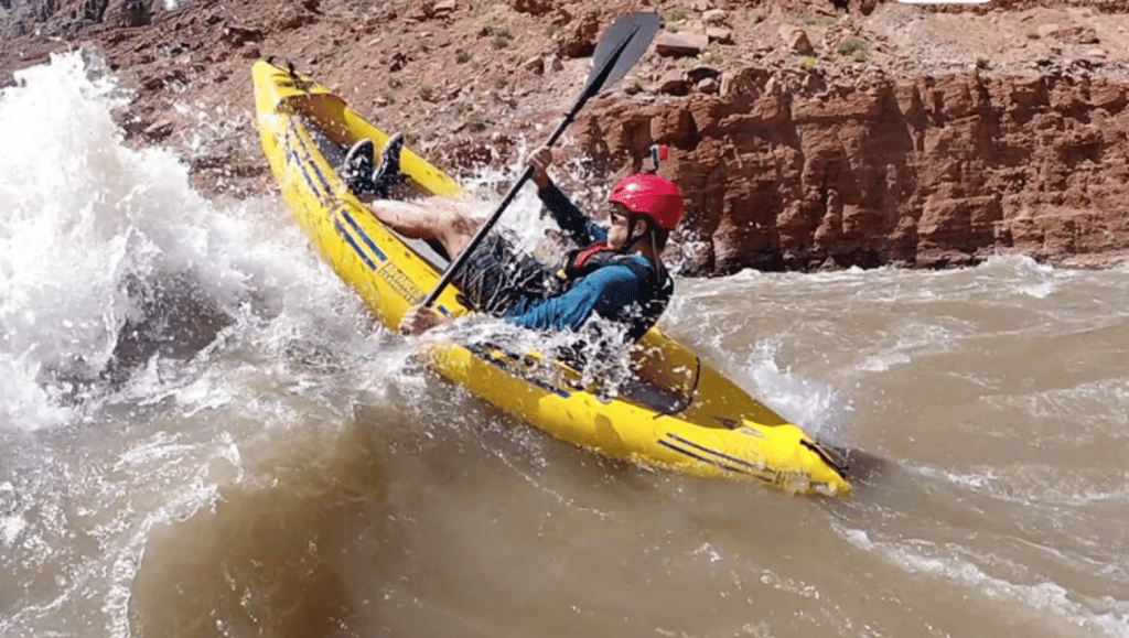 A whitewater kayaker powers through some rapids on an Advanced Elements Attack Pro whitewater inflatable kayak.