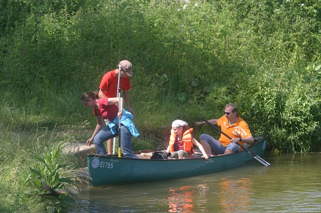 Mom, dad, and two teenagers land the canoe ashore after a canoe trip.