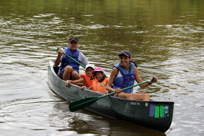 A family of 4 comfortably paddles a canoe