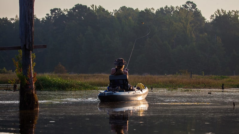 Sunrise photo of a kayak angler fishing in a shallow marsh