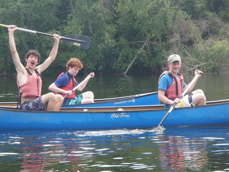 Teenagers have fun paddling an Old Town canoe.