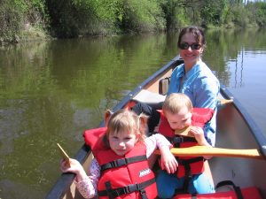 Mom sits in the stern of the canoe and poses for a photo with two young children in the middle.