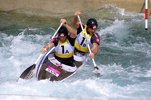 Olympic kayakers paddle a kayak in tandem