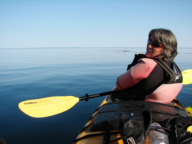 Older woman looks back for a photo as she kayaks a large, glassy lake