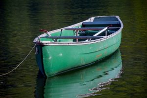 An empty, green square stern canoe is moored on a tranquil pond