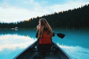 Woman seated at the front of a canoe paddles through glacial blue water