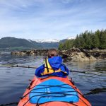 Woman in a blue hooded waterproof jacket sits in the front of a tandem kayak