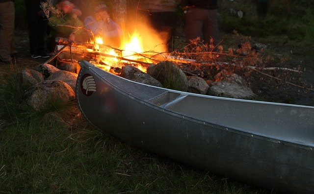 The stern of a canoe rests next to a warm and inviting evening campfire.